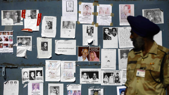 An Indian paramilitary soldier looks at the gate of an airport, covered with special announcements and pictures of missing people, in Jollygrant, in the northern Indian state of Uttarakhand, India, Wednesday, June 26, 2013. Paramilitary soldiers on Wednesday recovered 20 bodies from a steep hillside in northern India where a helicopter crashed while on a mission to rescue people stranded in monsoon floods, the country's air force chief said. (AP Photo/Rafiq Maqbool)