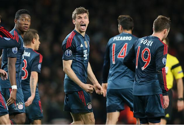 Bayern's Thomas Mueller, center, celebrates his side's second goal during a Champions League, round of 16, first leg soccer match between Arsenal and Bayern Munich at the Emirates stadium in L