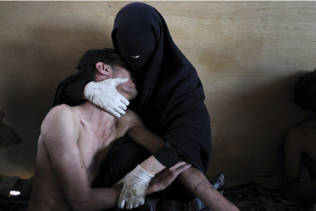 In this photo provided on Friday Feb. 10, 2012 by World Press Photo, the 2012 World Press Photo of the year by Samuel Aranda, Spain, for The New York Times, shows a woman holding a wounded relative du