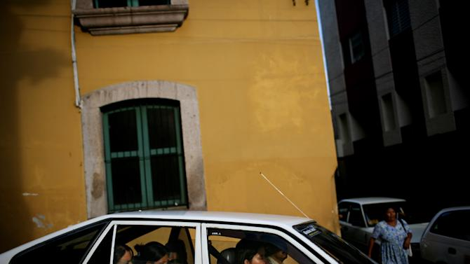 """FILE - In this Sept. 24, 2009 file photo, passengers ride in a taxi in downtown Tegucigalpa, Honduras. Taxi drivers are known to pay extortionists more than $500 a year to park on public property. During Christmas, the cabbies dish out another $500 each in holiday """"bonuses."""" This capital of 1.3 million people is a lawless place, but it does seem to have its own set of unwritten rules for living with the daily dangers. (AP Photo/Rodrigo Abd, File)"""