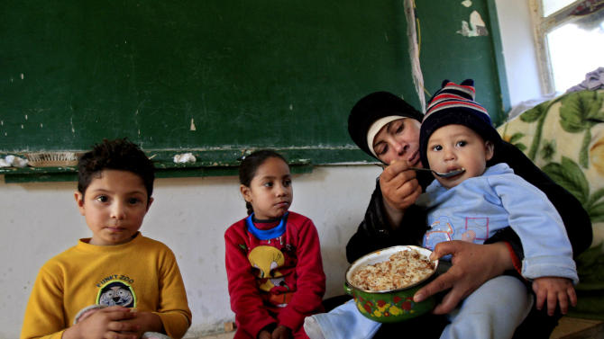 In this Tuesday, Jan. 15, 2013 photo, a Palestinian woman who fled her home in the Yarmouk camp for Palestinian refugees in south Damascus, feeds her baby inside a school, at the Ein el-Hilweh refugee camp, in the southern port city of Sidon, Lebanon. The Palestinian exodus from Syria has also revived decades-old debate over the Palestine refugees' 'right of return' to their homes that are now in Israel, adding to the complexity the conflict whose sectarian and ethnic overtones have spilled over into neighboring countries raising fears of a regional war. (AP Photo/Mohammed Zaatari)