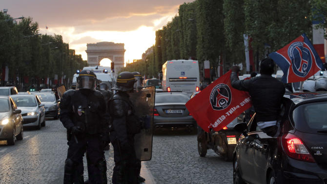 French riot police officers secure the Champs Elysees after some fans clashed with police during the celebrations of the French league one title win of Paris Saint-Germain soccer club, in Paris, Monday, May 13, 2013. (AP Photo/Christophe Ena)
