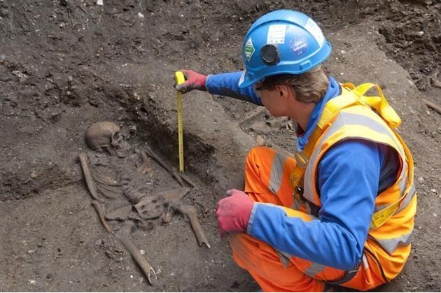 Photo issued on March 15, 2013 shows a Crossrail archaeologist uncovering a skeleton found in a tunnel shaft in London