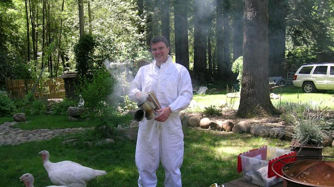 This undated photo provided by Love Creek Farm shows Jason Oeh as he prepares to work on bee hives, while the pet turkeys, Ariala and Rhoslyn, who are social and curious freely walk around in the yard.(AP Photo/Love Creek Farm)