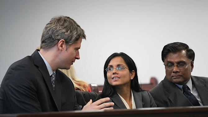 Former state lab chemist Annie Dookhan, center, speaks with her lawyer Nick Gordon, left, at Middlesex Superior Court as she waits for her for arraignment to begin with her father, Rasheed Khan, on Wednesday, Jan. 9, 2013, in Woburn, Mass. Dookhan pleaded not guilty to three counts of obstruction of justice.  She is charged in connection with altering drug evidence during the testing process and obstructing justice. Prosecutors allege Dookhan fabricated test results and tampered with drug evidence while testing substances in criminal cases.  (AP Photo/The Boston Globe, Suzanne Kreiter, Pool)