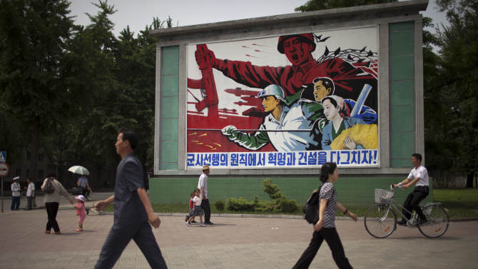 """People walk past a roadside propaganda billboard promoting the """"military first"""" policy and a boost to build the country's economy in Pyongyang, North Korea, Sunday, June 16, 2013. North Korea's top governing body on Sunday proposed high-level nuclear and security talks with the United States in an appeal sent just days after calling off talks with rival South Korea. (AP Photo/Alexander Yuan)"""