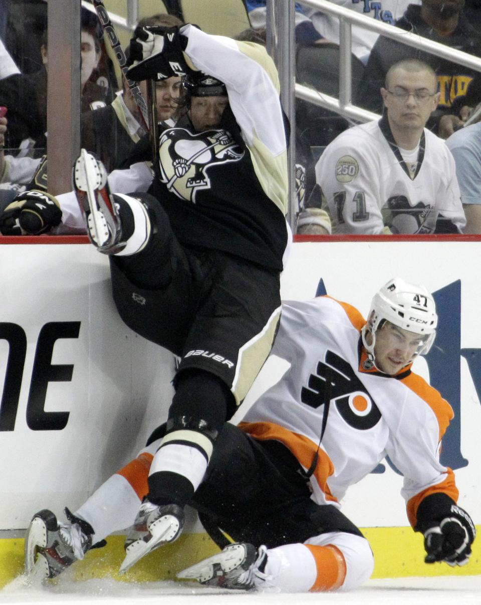 Pittsburgh Penguins' Arron Asham, left, collides with Philadelphia Flyers' Eric Wellwood (47) in the second period of Game 1 of an opening-round NHL hockey playoff series Wednesday, April 11, 2012, in Pittsburgh. (AP Photo/Gene J. Puskar)