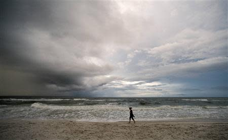A beachgoer takes an early morning walk as storm clouds from a weakening Tropical Depression Karen approach Orange Beach