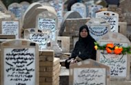 An Iraqi woman sits next to the grave of a relative at the al-Ghazali cemetery in Baghdad on the first day of Eid al-Adha on Friday. Shiite pilgrims in Iraq typically use the four-day Eid al-Adha holiday, which began on Friday, to either visit relatives, the graves of dead family members, or shrines to key figures in Shiite Islam located across the country