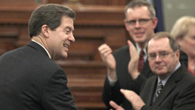 FILE - In this Jan. 11, 2012, file photo, Gov. Sam Brownback greets legislators before his annual State of the State address at the Kansas Statehouse in Topeka, Kan. A prosector said Tuesday, Aug. 21, 2012, that private dinners the Republican governor hosted for lawmakers at his official residence didn't substantially violate the state's opening meetings law even though they touched upon his legislative agenda (AP Photo/Charlie Riedel)