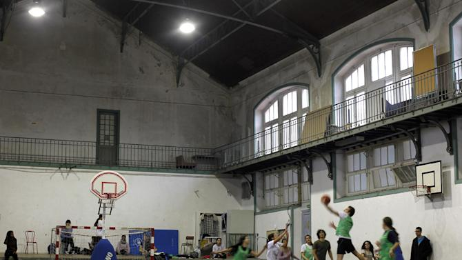 In this photo taken on March 8, 2013, students play basketball in a indoor sports hall of the Camoes high-school in Lisbon. The high school, one of the country's oldest and most prestigious, is a vivid demonstration of what happens when austerity is heaped on austerity. There are broken windows, cracked walls, flaking paint, ceilings stained by leaks, and sunscreens hanging off their hinges. (AP Photo/Francisco Seco)