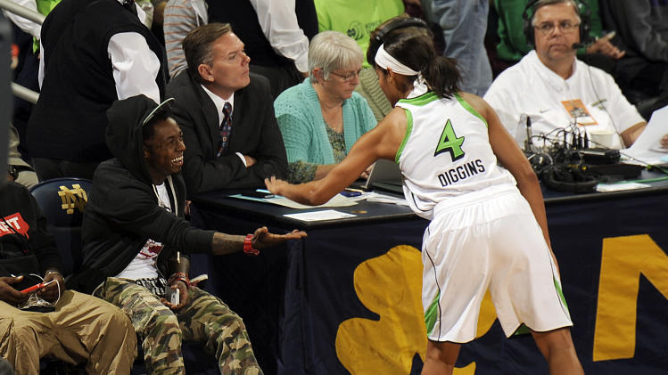 Rapper Lil Wayne, left, shakes hands with Notre Dame guard Skylar Diggins during second-half action of an NCAA college basketball game against Baylor, Wednesday, Dec. 5, 2012, in South Bend, Ind. Baylor won 73-61. (AP Photo/Joe Raymond)
