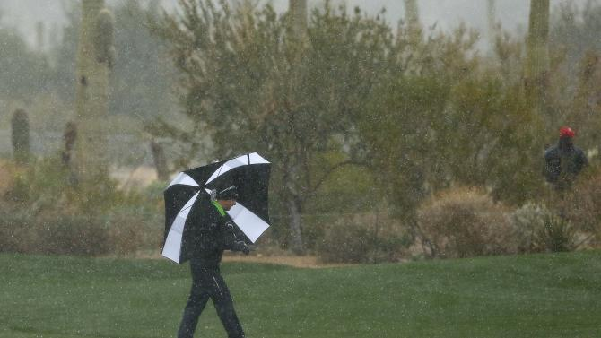 CORRECTS DAY AND DATE - Hunter Mahan makes his way along the 10th fairway as snow and rain fall during the Match Play Championship golf tournament, Wednesday, Feb. 20, 2013, in Marana, Ariz. Play was suspended. (AP Photo/Ross Franklin)