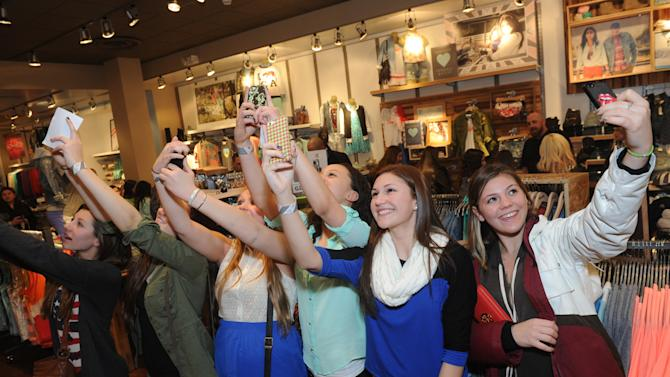 Fans capture the moment while waiting in line to meet Kendall and Kylie Jenner during their PacSun public appearance to launch the exclusive Kendall & Kylie collection, Friday, February 8, 2013, on Long Island, New York.   (Photo by Diane Bondareff/Invision for PacSun/AP Images)