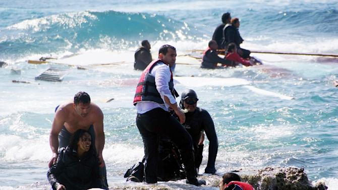 Greek rescue workers help a woman after a boat carrying migrants sank off the island of Rhodes, on April 20, 2015