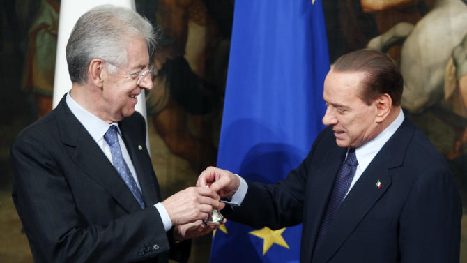 Italian premier Mario Monti, left, receives a small bell from former premier Silvio Berlusconi at Chigi palace premiers office after the swearing ceremony, in Rome Wednesday, Nov. 16, 2011. The bell is used by the Prime Minister to call for attention during cabinet meetings. (AP Photo/Pier Paolo Cito)
