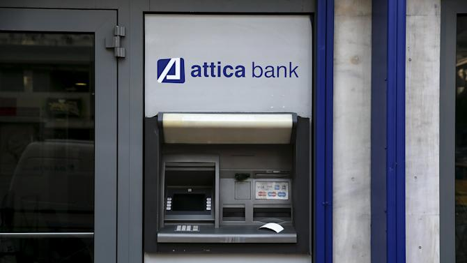 A transaction receipt is seen on an ATM outside a closed Attica Bank branch in Athens
