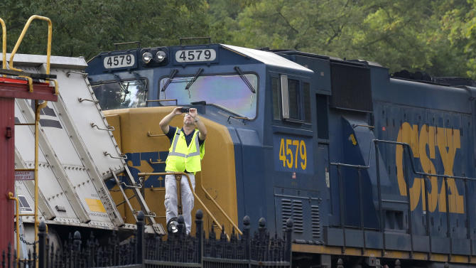An official photographs derailed train cars after a CSX freight train hauling coal derailed overnight in Ellicott City, Md., Tuesday, Aug. 21, 2012. Authorities said two people not employed by the railroad were killed in the incident. (AP Photo/Patrick Semansky)