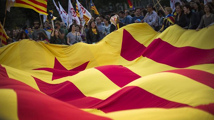 "In this June 2, 2014 photo, demonstrators wave a pro-independence ""estelada"" flag during a protest calling for the independence and the implementation of the republic in Catalonia after the announcement of the abdication of Spain's King Juan Carlos in Barcelona, Spain. (AP Photo/Emilio Morenatti)"