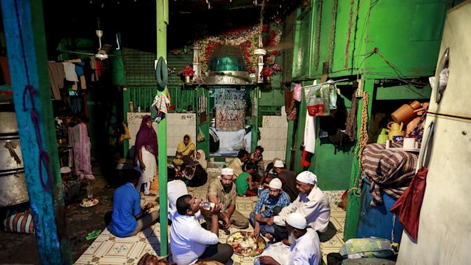 Muslims eat their Iftar (breaking of fast) meal during the holy month of Ramadan inside a shrine in Mumbai,