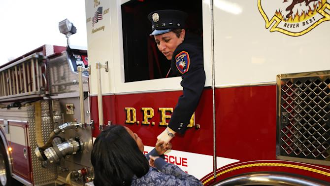IMAGE DISTRIBUTED FOR MACY'S - Make-A-Wish kid Christy, 13, thanks members of the Deer Park Fire Department at Macy's during National Believe Day, Friday, Dec. 14, 2012, in Huntington Station, NY. For every letter collected, Macy's donates $1 to Make-A-Wish, up to $1 million. On December 14, National Believe Day, Macy's will donate one additional $1, up to $500,000, to Make-A-Wish for each letter received. (John Minchillo/AP Images for Macy's)