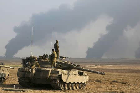 Israeli soldiers stand atop a tank outside the northern Gaza Strip