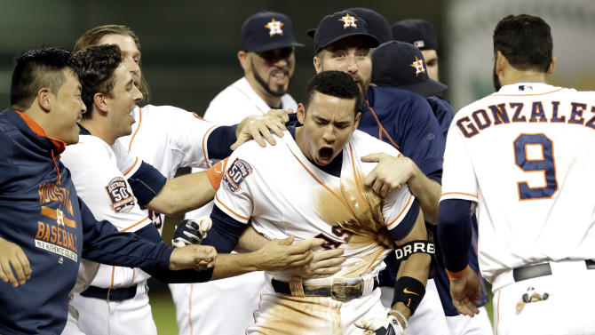 FILE - In this Aug. 19, 2015, file photo, Houston Astros' Carlos Correa, center, is mobbed by teammates after driving in the game-winning in the 13th inning of a baseball game to beat the Tampa Bay Rays 3-2 in Houston. Correa was selected as the AL Rookie of the Year on Monday, Nov. 16, 2015. (AP Photo/Pat Sullivan, File)