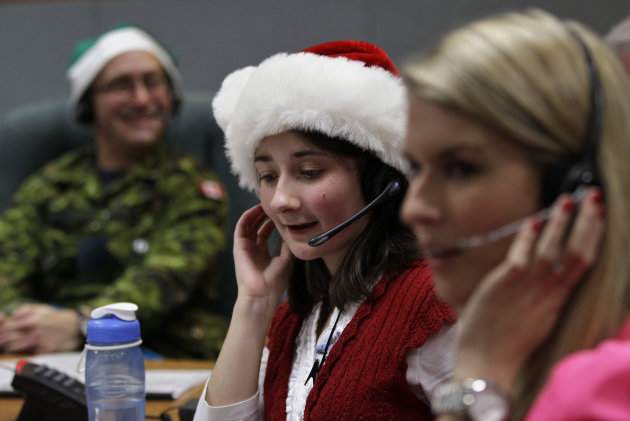 Volunteer Katherine Beaupre takes phone calls from children asking where Santa is and when he will deliver presents to their house, during the annual NORAD Tracks Santa Operation, at the North American Aerospace Defense Command, or NORAD, at Peterson Air Force Base, in Colorado Springs, Colo., Monday Dec. 24, 2012. Over a thousand volunteers at NORAD handle more than 100,000 thousand phone calls from children around the world every Christmas Eve, with NORAD continually projecting Santa's supposed progress delivering presents. (AP Photo/Brennan Linsley)
