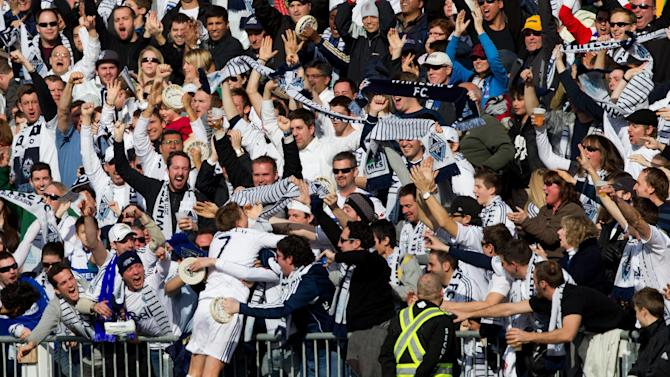 Vancouver Whitecaps' Terry Dunfield jumps into the crowd to celebrate his goal against the Toronto FC during the first half of an MLS soccer game in Vancouver, British Columbia on Saturday March 19, 2011. (AP Photo/The Canadian Press, Darryl Dyck)