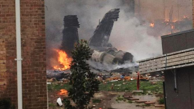 The burning fuselage of an F/A-18 Hornet lies smoldering after crashing into a residential building in Virginia Beach, Va., Friday, April 6, 2012. The Navy did not immediately return telephone messages left by The Associated Press, but media reports indicate the two aviators were able to eject from the jet before it crashed. They were being treated for injuries that were not considered life threatening. (AP Photo/Kandice Angel)