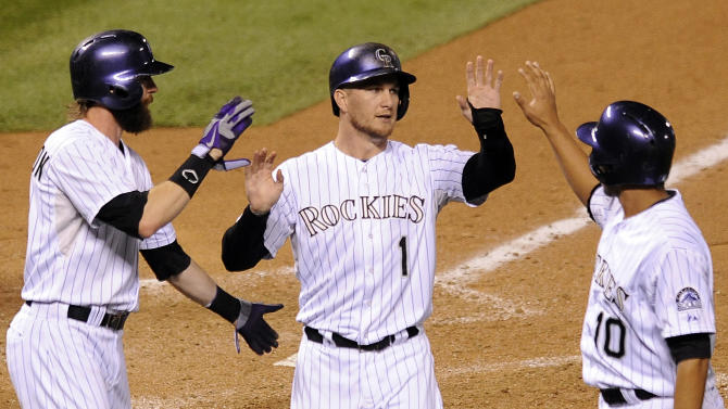 Colorado Rockies' Charlie Blackmon, left, and Cristhian Adames, right, congratulate Brandon Barnes, center, after they scored on a double by Michael Cuddyer in the eighth inning of a baseball game against the Arizona Diamondbacks, Friday, Sept. 19, 2014, in Denver. The Rockies won 15-3. (AP Photo/Chris Schneider)