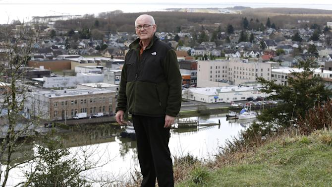 Jack Durney, mayor of Hoquiam, Wash., stands on a hill on Monday, March 18, 2014, overlooking his city, the Hoquiam River, and Grays Harbor. Because most of Hoquiam lies in the flood plain, Durney says possible increases in federal flood insurance rates would adversely affect many who live in his town. In the old logging port on an estuarine bay, the great majority of the 8,700 residents live in a flood hazard area. (AP Photo/Ted S. Warren)