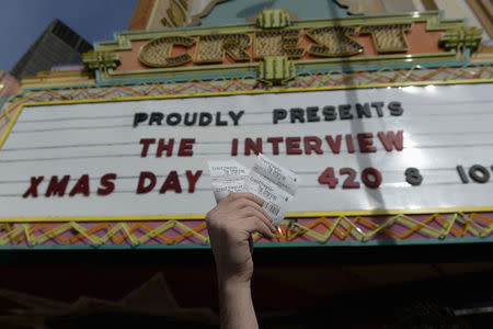 "Tickets for the film ""The Interview"" is seen held up by Melancon for the media at Crest Theater in Los Angeles"