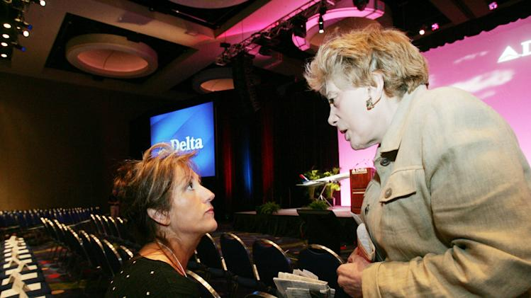 "FILE - In this Thursday, May 19, 2005 file photo, shareholder activist Evelyn Y. Davis, right, talks with a Delta associate who did not want to be identified at the Georgia International Convention Center, the site of the Delta Air Lines shareholders meeting, in College Park, Ga. For decades, Davis, who has been buying a few shares of big companies, attends their annual meetings, turning them into her personal stage. But in 2012, Davis didn't show up at any company's annual meeting. Age has finally made her do what the most powerful CEOs in America couldn't: Give it a rest. ""I'm not so young anymore,"" said Mrs. Davis, 82. (AP Photo/Ric Feld)"