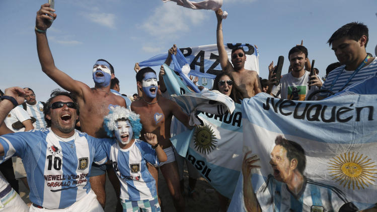 Argentina soccer fans celebrate their team's victory over Iran after a live telecast of the World Cup match inside the FIFA Fan Fest area on Copacabana beach, in Rio de Janeiro, Brazil, Saturday, June 21, 2014. Argentina won 1-0