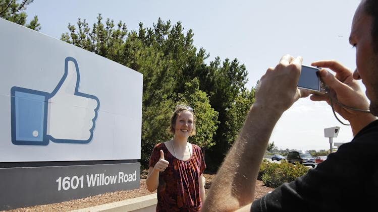 German tourists who use Facebook, take pictures outside of Facebook headquarters in Menlo Park, Calif., Friday, Aug. 17, 2012. Facebook stock is trading at $19 and has lost half its market value since its May public offering. (AP Photo/Paul Sakuma)