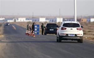 File photo of a police officer stopping a car to check for identifications at a checkpoint near Lukqun