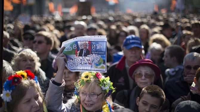 "A woman, wearing a traditional Ukrainian wreath of flowers on her head, holds up a sign with President Vladimir Putin's picture and the words: ""Stop lying!"" during a rally against pro-Putin media in Moscow, Russia, Sunday, April 13, 2014. More than 10,000 people have turned out in Moscow for an anti-Kremlin rally to denounce Russian state television's news coverage, particularly of the crisis in neighboring Ukraine. (AP Photo/Alexander Zemlianichenko)"