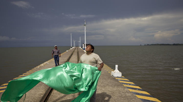 A worker prepares a flag to hang on the wharf off the shores of Cocibolca Lake, also known as Nicaragua Lake, in Granada, Nicaragua, Friday, June 7, 2013. A concession to build a canal across Nicaragua linking the Pacific Ocean and Caribbean Sea, which would go through the waters of Lake Nicaragua, will be awarded to a Chinese company, the National Assembly president said Wednesday. (AP Photo/Esteban Felix)