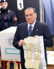 Former Prime Minister Silvio Berlusconi shows the electoral ballots before casting his vote at the polling station in Milan, February 24, 2013. Italians began voting on Sunday in one of the most closely watched elections in years, with markets nervous about whether it can produce a strong government to pull Italy out of recession and help resolve the euro zone debt crisis. REUTERS/Stefano Rellandini