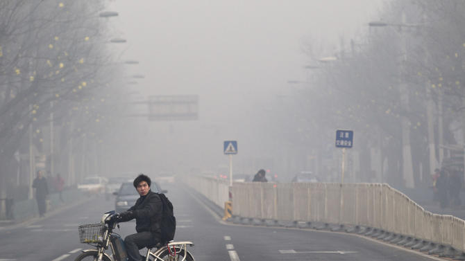 FILE - In this Jan. 10, 2012 file photo, a man rides an electric bike crossing a street shrouded by haze in Beijing. A senior Chinese environmental official told foreign embassies on Tuesday, June 5, 2012 to stop publishing their own reports on air quality in China, a clear reference to a popular U.S. Embassy Twitter feed that tracks pollution in smoggy Beijing. (AP Photo/Andy Wong, File)