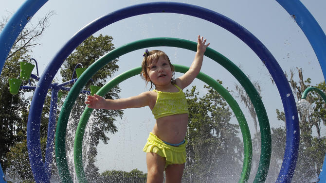 FILE - In this June 14, 2011 file photo, Alivia Parker, 21 months, runs through circles of spraying water on a 100 degree day in Montgomery, Ala. Parker is wearing sunscreen with an SPF of 100. Sunbathers headed to the beach this summer will find new sunscreen labels on store shelves that are designed to make the products more effective and easier to use. But despite those long-awaited changes, many sunscreens continue to carry SPF ratings that some experts consider misleading and potentially dangerous, according to a consumer watchdog group. (AP Photo/Dave Martin, File)