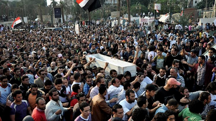 Egyptians carry the body of Gaber Salah, who was who was killed during clashes with security forces in Cairo, Egypt, Monday, Nov. 26, 2012. Thousands of Egyptians on Monday gathered into Cairo's Tahrir Square to attend the funeral of Salah, who was severely injured during clashes with security forces last week and died Sunday night. (AP Photo/Hussein Tallal)