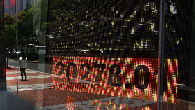 A woman walks past a bank electronic board showing the Hong Kong share index outside a Hong Kong local bank Wednesday, July 3, 2013. Asian stocks slid on Wednesday as Egypt's unfolding political crisis pushed the price of oil to its highest level in more than a year, adding to an uncertain global economic outlook. Hong Kong's Hang Seng dropped 1.8 percent to 20,281.62. (AP Photo/Vincent Yu)