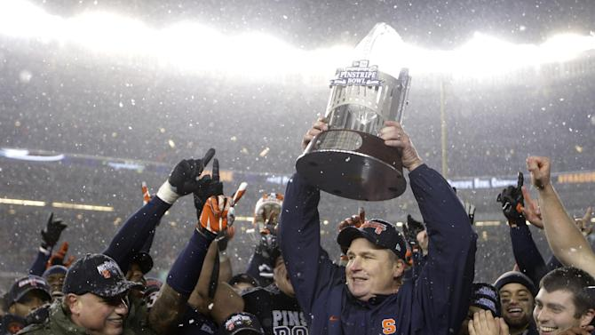 New York Yankees president Randy Levine, left, and chief operating officer Lonn Trost, center left, react after presenting the Pinstripe Bowl trophy to Syracuse coach Doug Marone after Syracuse defeated West Virginia 38-14 in the Pinstripe Bowl NCAA college football game at Yankee Stadium in New York, Saturday, Dec. 29, 2012. (AP Photo/Kathy Willens)