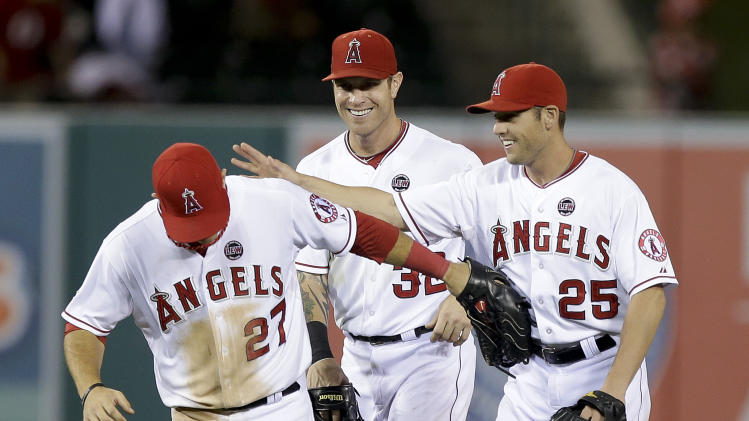 Los Angeles Angels center fielder Mike Trout, left, Josh Hamilton and Peter Bourjos celebrates their 10-9 win against the Seattle Mariners during a baseball game in Anaheim, Calif., Thursday, June 20, 2013. (AP Photo/Chris Carlson)