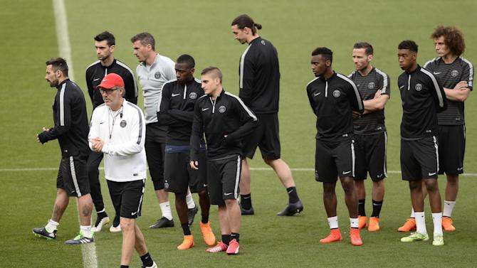 Paris Saint Germain's coach Laurent Blanc, second left, attends a training session with his players at Camp Nou stadium in Barcelona, Spain, Monday, April 20, 2015.  FC Barcelona will play against Paris Saint Germain in a quarterfinal Champions League second leg soccer match on Tuesday April 21. (AP Photo/Manu Fernandez)