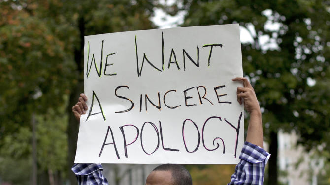A man holds a sign during a protest against Lewiston Mayor Robert Macdonald Thursday, Oct. 4, 2012 in Lewiston, Me. Critics of the mayor delivered petitions asking for his resignation because of comments he made about Somali refugees in his city. (AP Photo/Robert F. Bukaty)