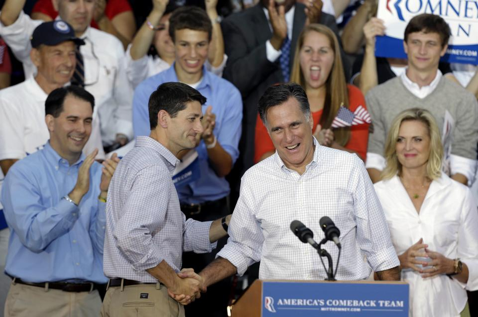 Republican presidential candidate Mitt Romney, right, is introduced by vice presidential running mate Rep. Paul Ryan, R-Wis., arrive during a welcome home rally, Sunday, Aug. 12, 2012, in Waukesha, Wis. At left is Wisconsin Gov. Scott Walker and Romney's wife Ann Romney, rear right. (AP Photo/Jeffrey Phelps)