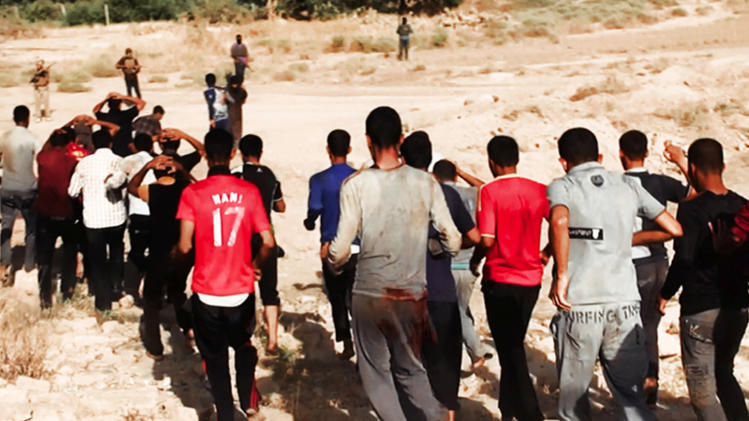 This image posted on a militant website on Saturday, June 14, 2014, which has been verified and is consistent with other AP reporting, appears to show militants from the al-Qaida-inspired Islamic State of Iraq and the Levant (ISIL) leading captured Iraqi soldiers wearing plain clothes to an open field moments before shooting them in Tikrit, Iraq. The Islamic militant group that seized much of northern Iraq has posted photos that appear to show its fighters shooting dead dozens of captured Iraqi soldiers in a province north of the capital Baghdad. Iraq's top military spokesman Lt. Gen. Qassim al-Moussawi confirmed the photos' authenticity on Sunday and said he was aware of cases of mass murder of Iraqi soldiers. (AP Photo via militant website)